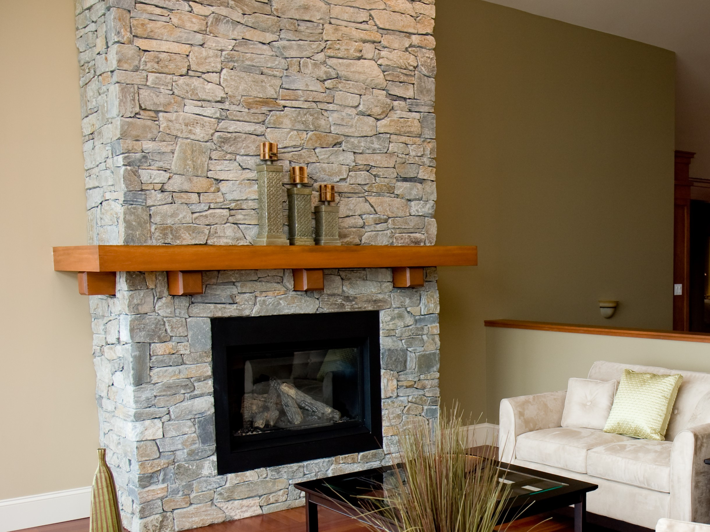 A stone fireplace and beautiful hardwood floors highlight the living room of a new luxury home.